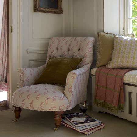 Susie Watson Designs -  Susie Watson Designs Fabric Collection - A pink and white armchair with plain and patterned olive green and white cushions, and a pink and green checked throw
