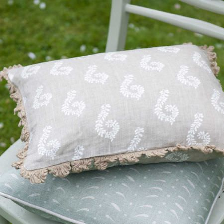 Susie Watson Designs -  Susie Watson Designs Fabric Collection - A white pattern printed on a light grey cushion with beige fringing, on a light blue patterned cushion, on a pale chair