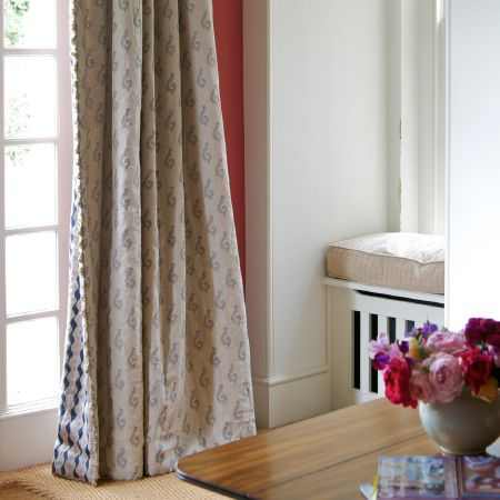 Susie Watson Designs -  Susie Watson Designs Fabric Collection - Double-sided curtains with different grey and beige patterns on each side, with a cream rug, a wooden table and a round vase