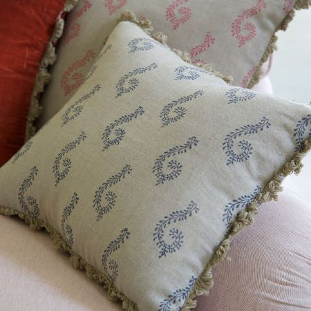 Susie Watson Designs -  Susie Watson Designs Fabric Collection - Three cushions with beige fringing; one in red, one in grey with a pink pattern, and one in grey with a blue pattern