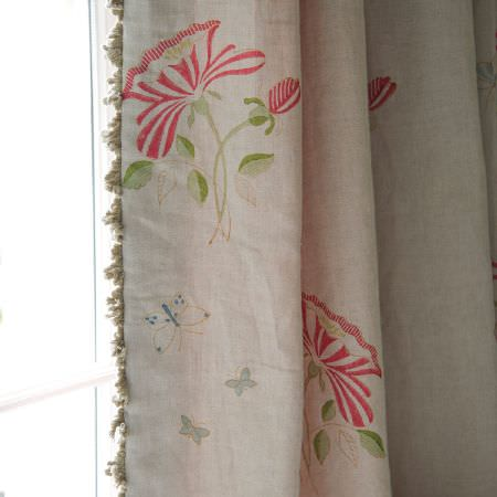 Susie Watson Designs -  Susie Watson Designs Fabric Collection - Floral patterned curtains with a red, green and grey design on a cream-grey background, with grey fringing down the edge