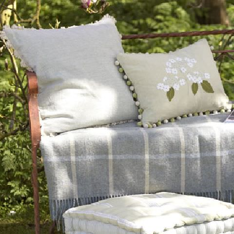 Susie Watson Designs -  Susie Watson Designs Fabric Collection - Blue fringed throw with white stripes. Neutral fringed cushion and pale green bobble-edged cushion with white floral design.