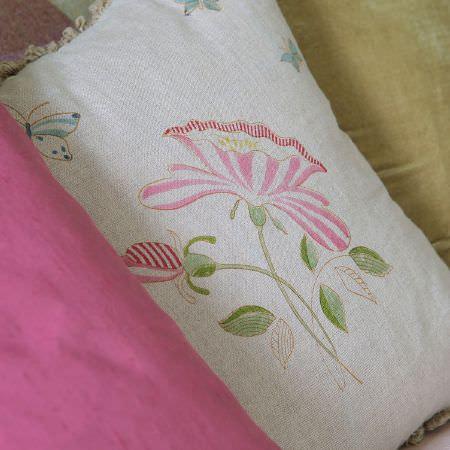 Susie Watson Designs -  Susie Watson Designs Fabric Collection - An off-white, pink, green and pale blue floral and butterfly print cushion placed between plain green and pink cushions