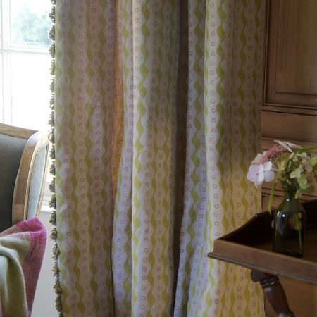 Susie Watson Designs -  Susie Watson Designs Fabric Collection - A wooden table with a glass vase beside green, pink and white patterned, fringed curtains, by a chair with a checked throw