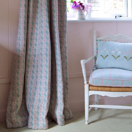 Susie Watson Designs -  Susie Watson Designs Fabric Collection - Pink, blue and white patterned curtains beside matching checked and floral cushions on a white wood chair with a wicker seat