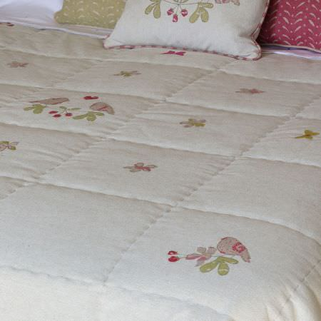 Susie Watson Designs -  Susie Watson Designs Fabric Collection - An off-white quilt with a green, beige and red floral and bird print, with patterned cushions including a matching design