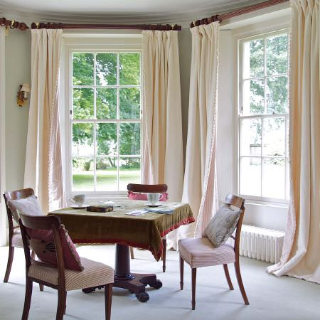 Susie Watson Designs -  Susie Watson Designs Fabric Collection - Dark wood table and chairs with padded patterned fabric seats, with an olive green tablecloth and plain cream curtains