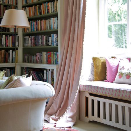 Susie Watson Designs -  Susie Watson Designs Fabric Collection - Plain light pink curtains with a cream sofa, a tall cream floor lamp, and multicoloured window seat and scatter cushions