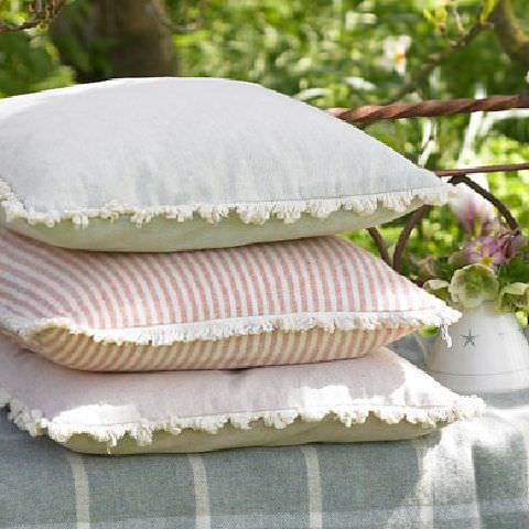 Susie Watson Designs -  Susie Watson Designs Fabric Collection - Blue throw with white stripes forming squares. Pastel pink and eau de nils fringed cushions and pink striped fringed cushion.
