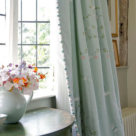 Susie Watson Designs -  Susie Watson Designs Fabric Collection - A hemispherical wood table with a large jug vase, and curtains with pinstripes one one side and flowers and birds on the other