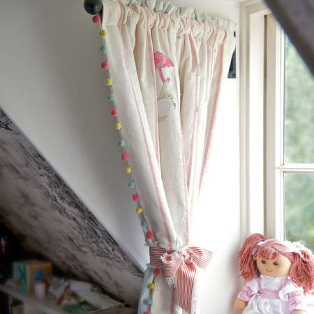 Susie Watson Designs -  Susie Watson Designs Fabric Collection - Cream, pink and grey patterned curtains with pink, green and blue pompom edges, tied with striped ribbon, beside a rag doll