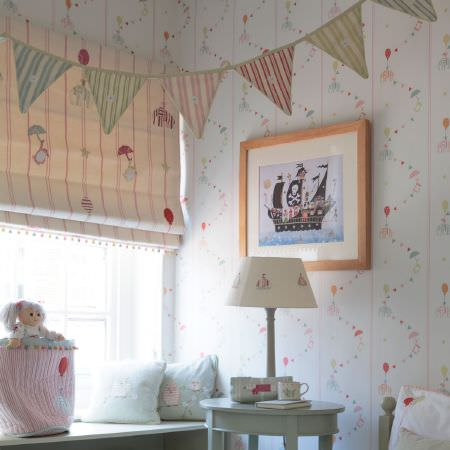 Susie Watson Designs -  Susie Watson Designs Fabric Collection - Patterned wallpaper, striped bunting, a striped and patterned blind, a small table, a lamp, cushions, a bag and a rag doll