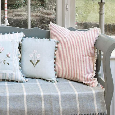 Susie Watson Designs -  Susie Watson Designs Fabric Collection - Pale blue fringed throw with white stripes forming squares. Fringed pink striped cushion, blue bobble-edged cushion and striped cushion.