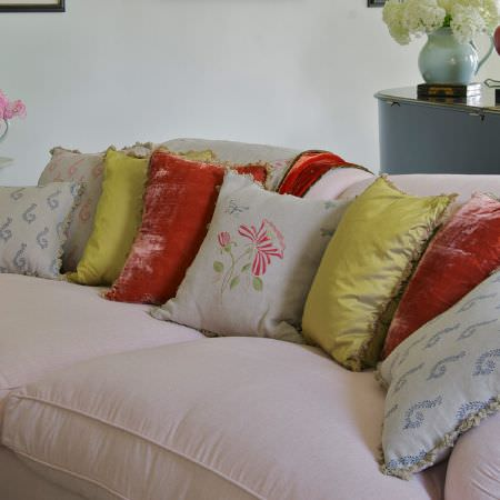 Susie Watson Designs -  Susie Watson Designs Fabric Collection - A sumptuous pale pink sofa with plain and patterned cushions in red, lime green and pale grey, with a round mirrored table