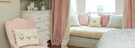 Susie Watson Designs -  Susie Watson Designs Fabric Collection - Pale pink, blue and yellow making up bedding, a striped armchair, cushions and curtains, with a white chest of drawers