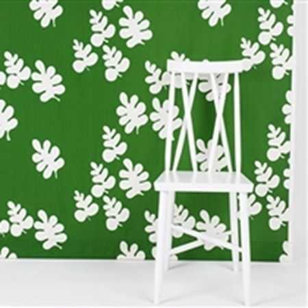 Swedish Fabric Company -  Boras Cotton Collection - A simple chair painted in white, in front of a wall covered in bright green with large, white stylised oak leaf shapes