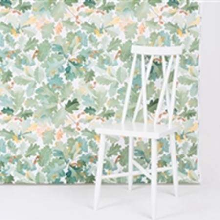 Swedish Fabric Company -  Boras Cotton Collection - Watercolour style oak leaves printed in various different shades of green over a wall, behind a simple white wood chair