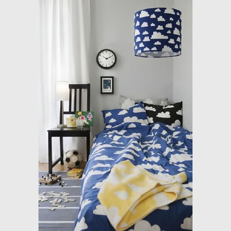 Swedish Fabric Company -  Farg and Form Fabric Collection - Dark blue bedding, a black pillow and lamp shade, and a yellow blanket, all with a white cloud print, beside a black chair and blue striped rug