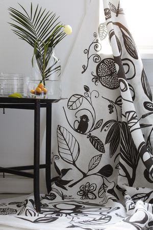 Swedish Fabric Company -  HappySTHLM Fabric Collection - White fabric with large, fun jungle print in black, with a black side table, glass jar type vase, and glass bowl