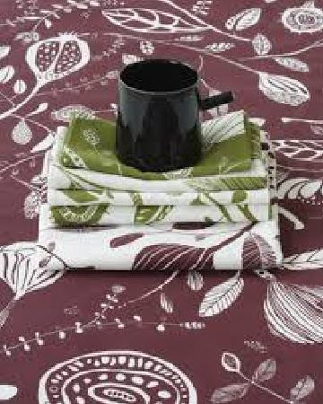 Swedish Fabric Company -  HappySTHLM Fabric Collection - Fabric with a purple-red background, stylised white floral pattern, swatches of matching green, purple and white fabric, and a black mug