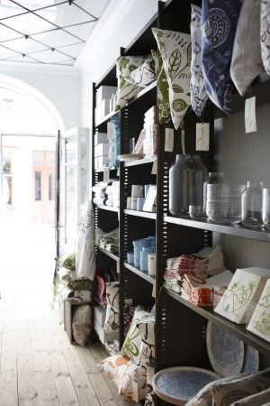 Swedish Fabric Company -  HappySTHLM Fabric Collection - Shelving unit stacked with patterned cushions, glass jar vases, crockery, patterned trays and tiles, fabrics, mugs, blue jugs, white boxes