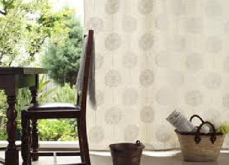 Swedish Fabric Company -  Kinnamark Fabric Collection - Beige curtains with faded grey circles, dark wood kitchen table and chair and a raffia shopping basket and pail.