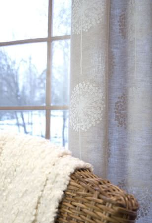 Swedish Fabric Company -  Kinnamark Fabric Collection - Silvery grey curtains with large white snowflake-like pattern, wicker chair with cream woollen fabric  folded loosely across back.