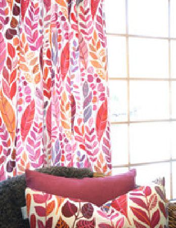 Swedish Fabric Company -  Kinnamark Fabric Collection - Bright leaf patterns of reds and pinks on white background, wicker chair with one cushion in similar pattern and one in deep pink.