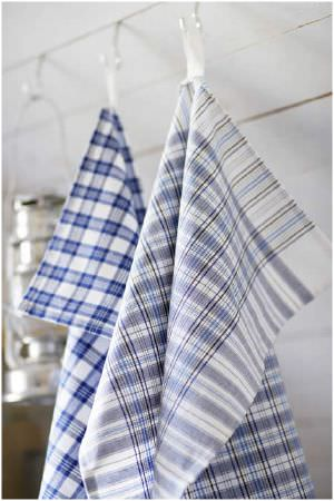 Swedish Fabric Company -  Linum Fabric Collection - Hanging white and blue checked fabrics, next to a hanging lantern