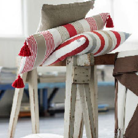 Swedish Fabric Company -  Linum Fabric Collection - Rustic wooden bench with tasseled red, beige and cream striped cushions, and one plain beige cushion