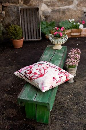 Swedish Fabric Company -  Mairo Fabric Collection - Green, garden Pembroke table with a white cushion with a bright pink abstract pattern.