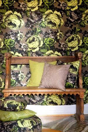 Swedish Fabric Company -  Mairo Fabric Collection - Wall pattern of large, dark green, cabbage-like roses with two similar patterned cushions and  plain cushions in yellow, beige and green.