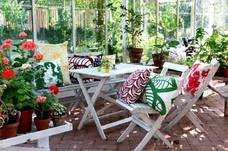 Swedish Fabric Company -  Mairo Fabric Collection - White conservatory chairs with cushions with large abstract patterns in bright green, yellow and reds.