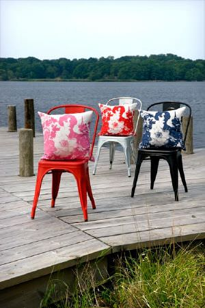 Swedish Fabric Company -  Mairo Fabric Collection - Three kitchen chairs each with a cushion depicting an abstract pattern in red, pink and dark blue.