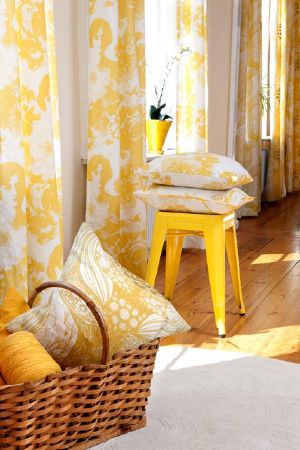 Swedish Fabric Company -  Mairo Fabric Collection - White curtains with bright yellow abstract pattern with matching cushions in wicker basket and on yellow kitchen stool.