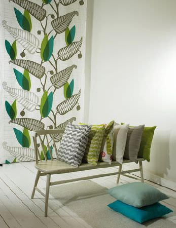 Swedish Fabric Company -  Spira Fabric Collection - Pale green wooden bench, with grey, green and cream cushions, two blue cushions and fabric with a large green fern design