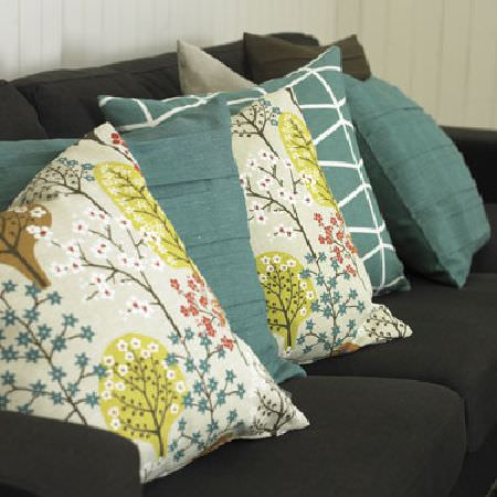 Swedish Fabric Company -  Spira Fabric Collection - Two plain, grey-green cushions, two cushions with beige background and small mulit-coloured flowers, and a grey-green cushion with white.