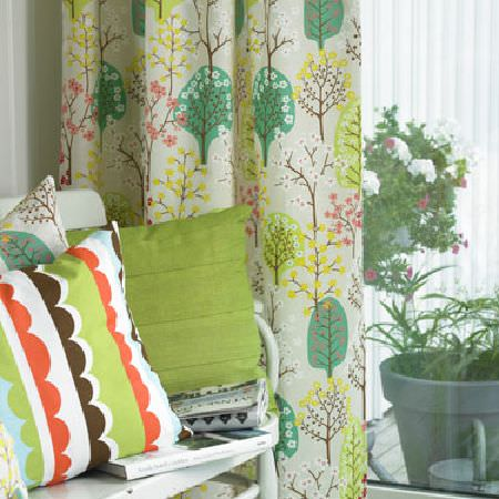 Swedish Fabric Company -  Spira Fabric Collection - Curtains with neutral background with green, pink and brown woodland pattern. Cushions in plain green and green, orange and white.