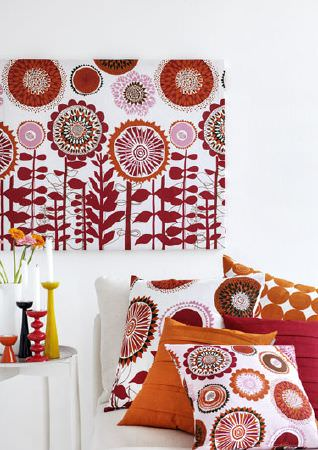Swedish Fabric Company -  Spira Fabric Collection - Wall hanging with white background and dark red floral pattern. Two cushions in similar material, and cushions in plain red and orange.