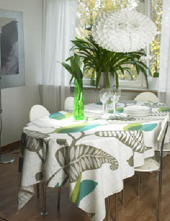 Swedish Fabric Company -  Spira Fabric Collection - White ruffle light shade above white and metal chairs, a table with a tablecloth in a large fern print, wine glasses and a green glass vase
