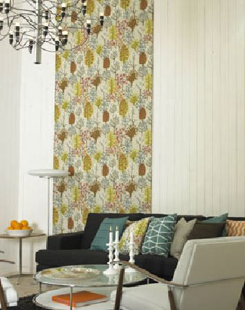 Swedish Fabric Company -  Spira Fabric Collection - Beige wall hanging with dark yellow and bracken leaf-type pattern. A beige and dark brown sofa with yellow, green and beige cushions.