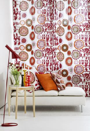 Swedish Fabric Company -  Spira Fabric Collection - Curtains with a white background  and geometric floral shapes in dark reds. Two cushion in a similar material and one in plain  orange.