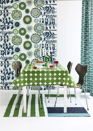 Swedish Fabric Company -  Spira Fabric Collection - Wall hanging with white background and geometric florals in green and blues; Curtains in green-grey with white pattern and green tablecloth.