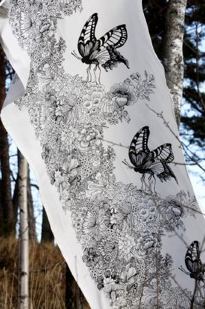 Swedish Fabric Company -  Vallila Fabric Collection - Fabric with white background and dramatic pattern of black and white butterflies and foliage.