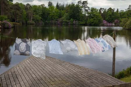 Titley and Marr -  Printed Fabric Fabric Collection - A wooden jetty beside a large lake, with 8 swatches of patterned fabrics in various colours hanging from a washing line