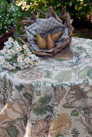 Titley and Marr -  Printed Fabric Fabric Collection - A bowl made out of twigs holding checked fabric and pears, beside a daisies on a table with a large, muted floral print