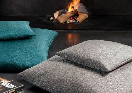 Wemyss -  Aros Fabric Collection - One large and one small ash grey square cushion, with one large and one small plain turquoise cushion, beside a fire