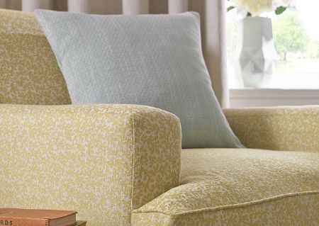 Wemyss -  Athena Fabric Collection - A plain, very pale blue coloured square scatter cushion, on a pale green and white armchair featuring a very small pattern