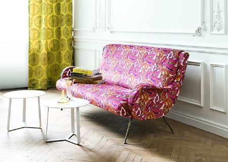 Wemyss -  Capri Fabric Collection - A modern, curved sofa covered with bright orange and pink paisley shapes, with citrus patterned curtains and 2 white tables