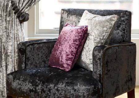 Wemyss -  Diva Fabric Collection - Luxurious velvet textures finishing a black armchair, silver curtains, and scatter cushions in silver and dark pink